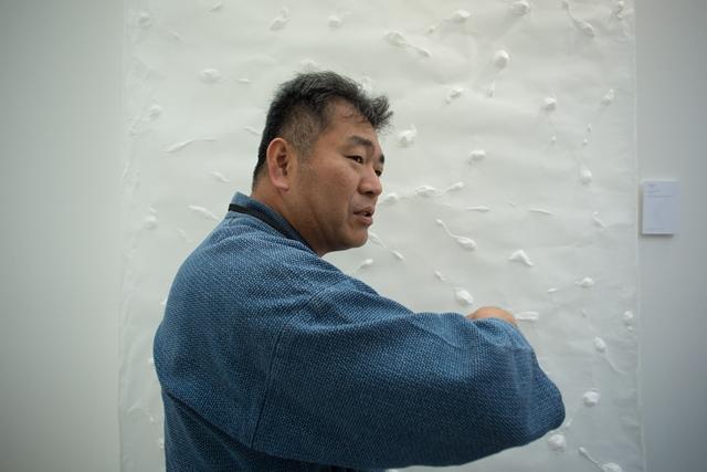 「手の和紙」の製法について、展示ブースで来場者に解説する谷口祐次郎さん。日本から持参した作務衣に身を包んで、和紙の世界を熱心にアピールした 写真:Julie Rousse