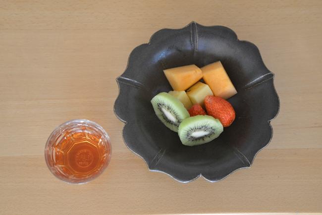 唐津焼作家、岡本作礼さんの黒高麗の縁飾り皿。スーパーマーケットで売られているパック入りのカットフルーツも、これに盛れば、もてなしとくつろぎの一品に(写真すべて:下川一哉)