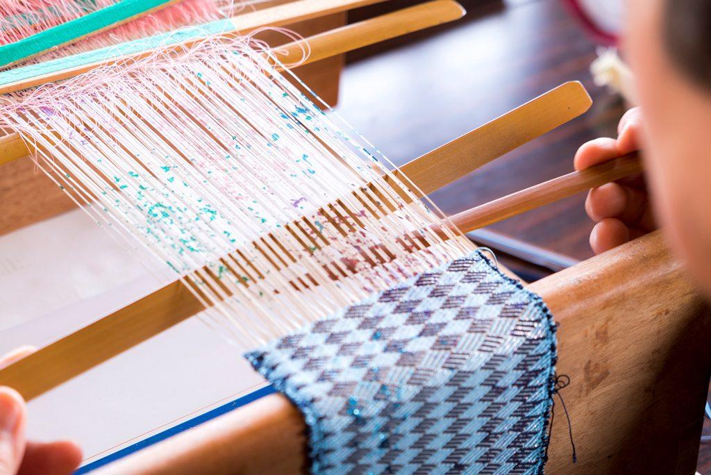 織り台にセットした経糸を竹べらで拾い緯糸を通す