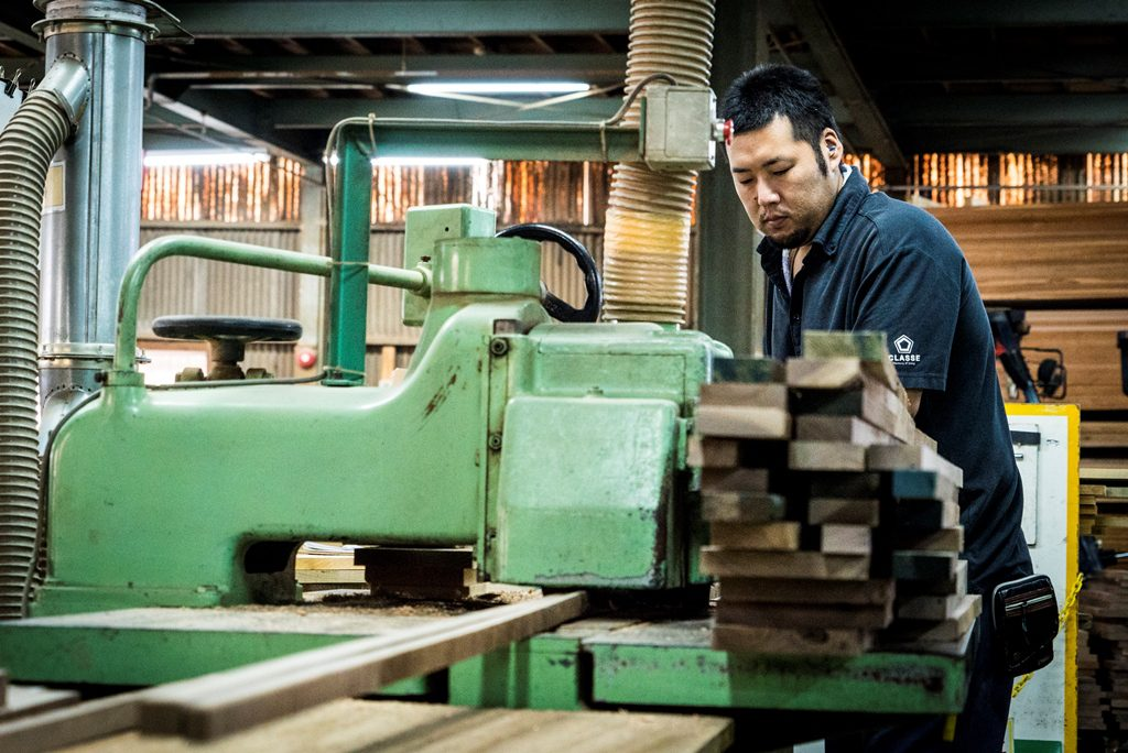 工場では機械を使って木材を切削する